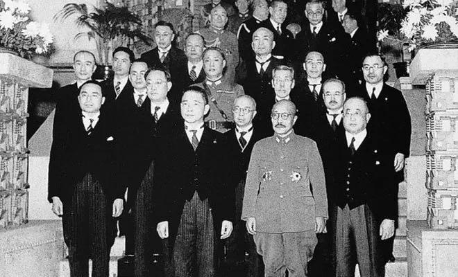 1942年12月23日,汪精卫与周隆庠(二排左一)、周佛海(二排左二)、徐良(二排左三)、梅思平(三排左一)、大东亚相青木一男(三排右一)等出席日本首相东条英机(前中)晚宴前合影。